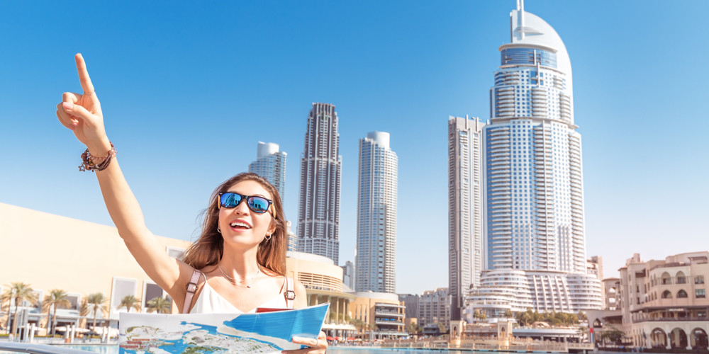Happy tourist girl with map travels in Dubai city
